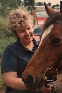 Maggie wearing a navy polo shirt whilst smiling and stroking a brown horse