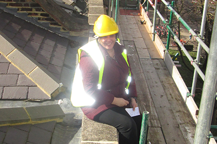 Ellie Achilleos, Capital Works Manager wearing a high vis jacket and a hard hat whilst sat on a roof at a construction site