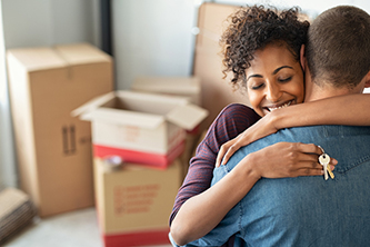 A young couple hugging as they celebrating moving into their new home.