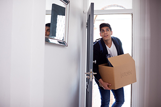 Young man with dark hair wearing a check shirt, holding a cardboard box whilst carrying through his new home