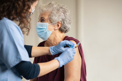 Elderly woman wearing a face mask receiving covid vaccine