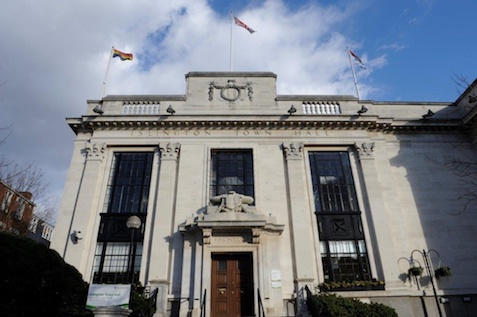 Islington Town hall with the Pride and Great Britain flags flying and a backdrop of a blue and cloudy sky