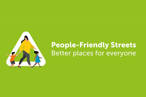 """Illustration - lime green background, with a woman wearing a yellow jumper, and walking across the road with 2 young children. """"People-Friendly Streets - Better places for everyone"""""""