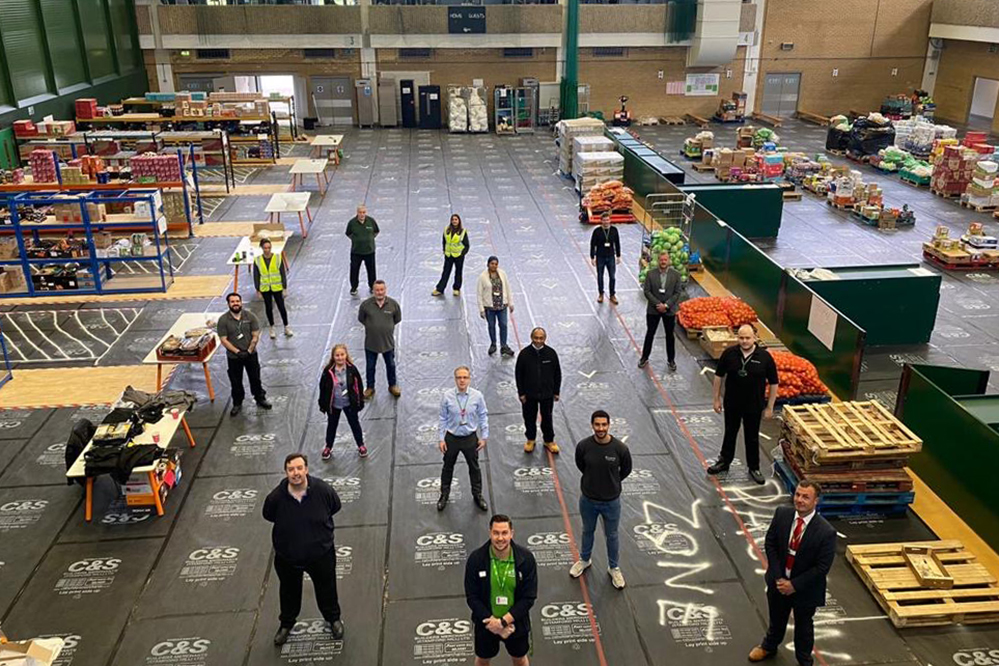 a group of Islington Council staff, standing socially distance in a food distribution warehouse, surrounded by packing stations and fresh produce